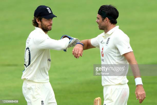 James Anderson of England 'elbow bumps' Ben Foakes after taking the wicket of Joe Denly of England during Day One of a England Warm Up Match at the...