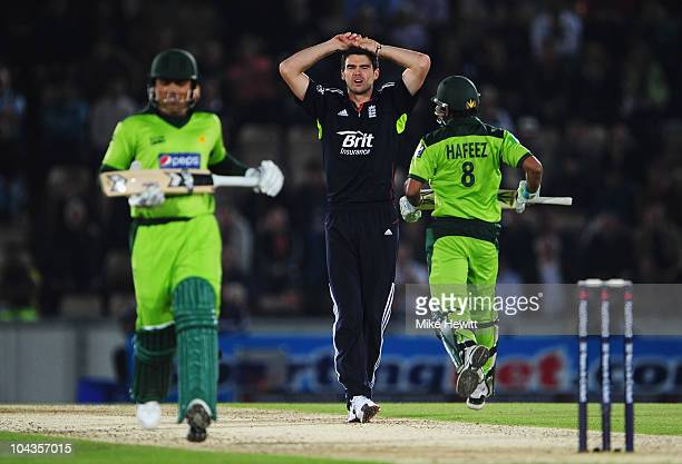 James Anderson of England holds his head as Kamran Akmal and Mohammad Hafeez of Pakistan run between the wickets during the 5th NatWest One Day...