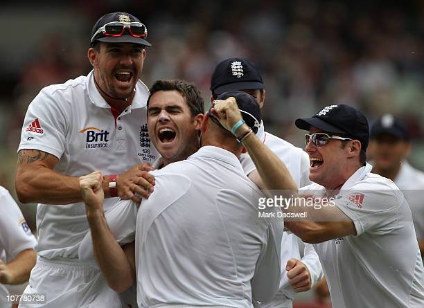 James Anderson of England is congratulated by teammates after taking the wicket of Michael Hussey of Australia during day one of the Fourth Test...