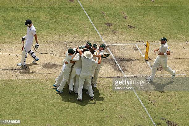 James Anderson of England leaves the field after losing his wicket as the Australia team celebrate victory and a 30 series win during day five of the...