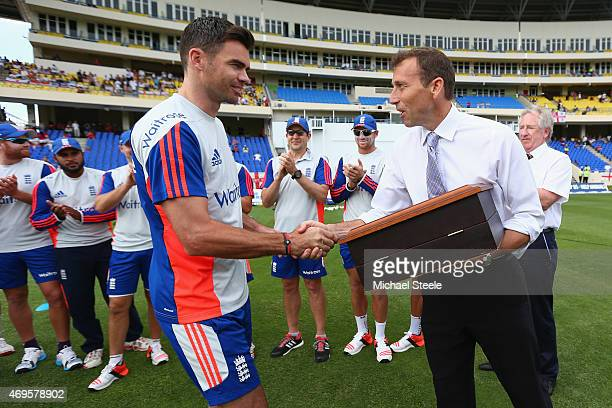 James Anderson of England making his 100th Test appearance is presented with a silver cap from ex England captain Michael Atherton during day one of...