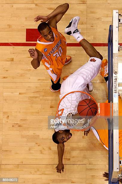 James Anderson of the Oklahoma State Cowboys drives to the hoop against JP Prince of the Tennessee Volunteers during the first round of the NCAA...