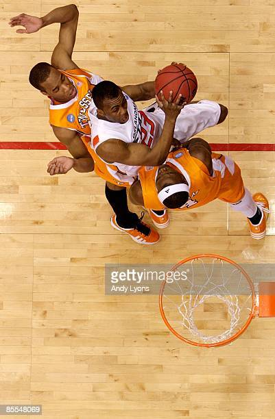 James Anderson of the Oklahoma State Cowboys drives to the hoop against Wayne Chism and JP Prince of the Tennessee Volunteers during the first round...
