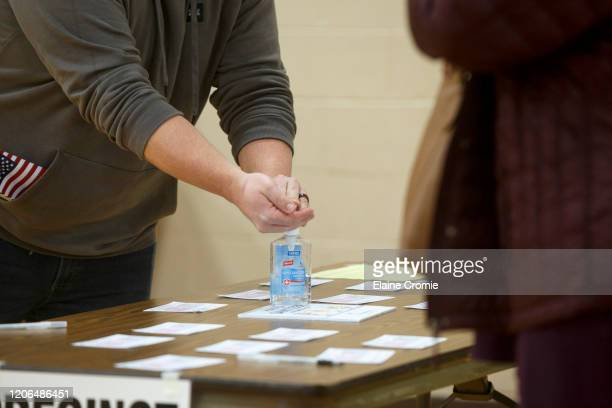 James Beavis uses hand sanitizer that the polling place provided after casting his ballot at Warren Woods Baptist Church on March 10, 2020 in Warren,...