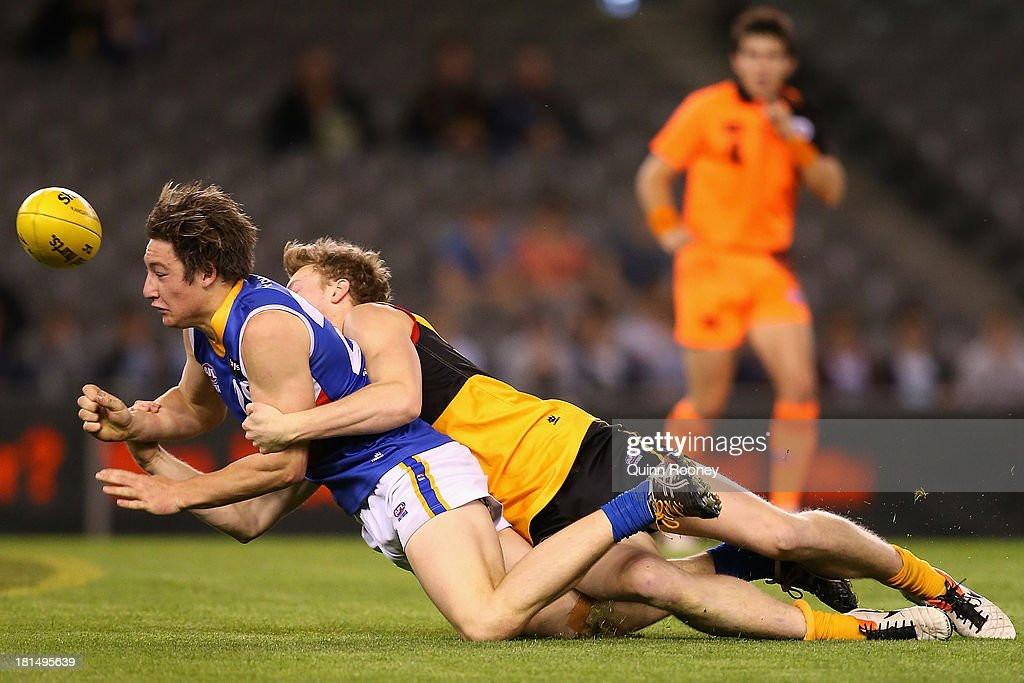 James Belo of the Ranges handballs whilst being tackled by James Hammond of the Stingrays during the TAC Cup final match between Eastern Ranges and the Dandenong Southern Stingrays at Etihad Stadium on September 22, 2013 in Melbourne, Australia.