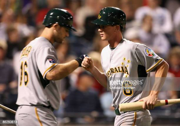 James Beresford of Team Australia is congratulated by Justin Huber after Beresford scored a run against the Seattle Mariners during the spring...