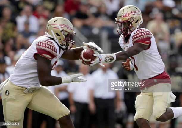 James Blackman of the Florida State Seminoles hands the ball off against hte Wake Forest Demon Deacons during their game at BBT Field on September 30...