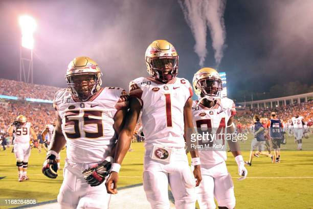 James Blackman of the Florida State Seminoles walks off the field between Dontae Lucas and Adarius Dent after the end of a game against the Virginia...