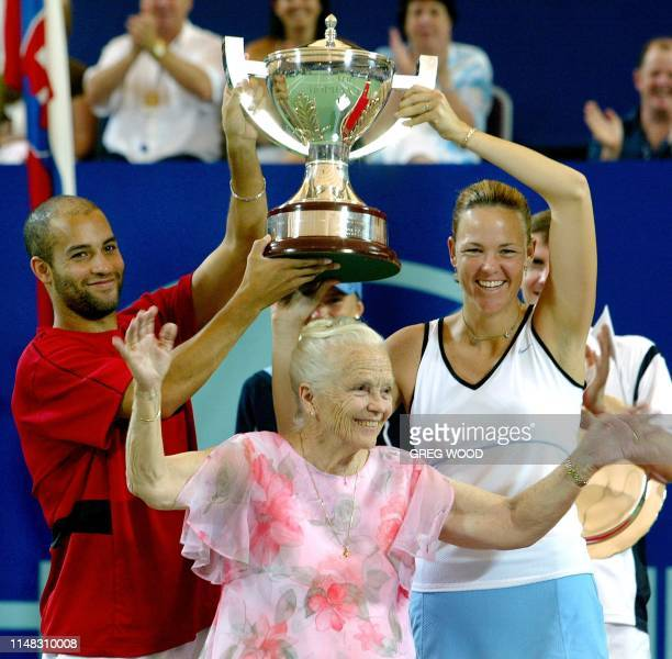 James Blake and compatriot Lindsay Davenport of the US joke with Lucy Hopman wife of the late Harry Hopman at the trophy presentation after they had...