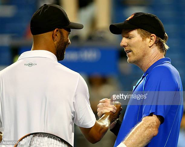 James Blake and Jim Courier greet each other after the Men's Legends match during the Connecticut Open at the Connecticut Tennis Center at Yale on...