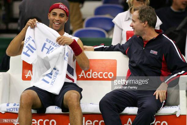 James Blake of the United States smiles with team Captain Patrick McEnroe on the bench during a changeover in his match against Dimitry Tursunov of...