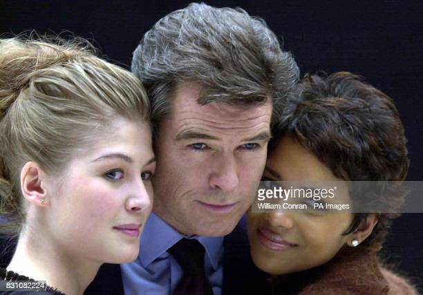James Bond actor Pierce Brosnan with actresses Rosamund Pike and Halle Berry during a photocall at Pinewood Studios north of London for 'Bond 20' the...