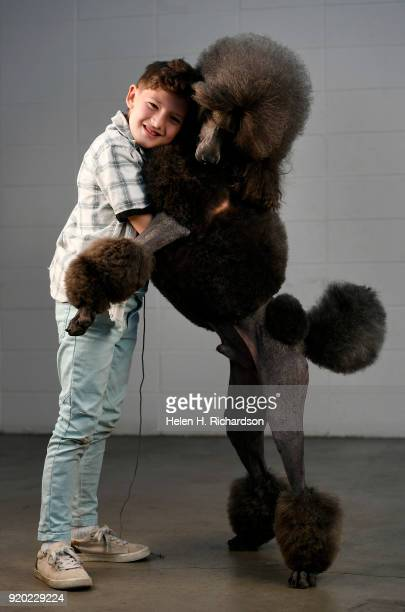 James Bond Adams poses for a portrait with his mother's three year old Standard Poodle Colorado Chrome during the Colorado Kennel Club Dog Show at...
