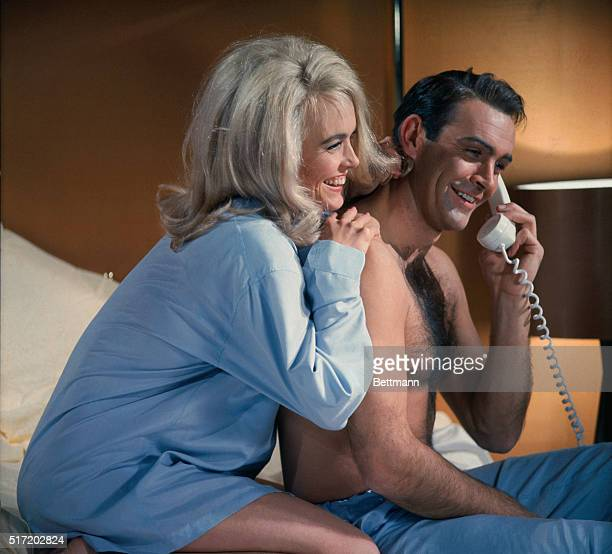 James Bond and Jill Masterson share a laugh on the phone in the James Bond flick, Goldfinger. 1964.