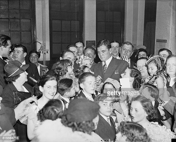 James Braddock former heavyweight title holder has quite a job autographing papers handed to him by admirers' as he attended a smoker at Carmelite...