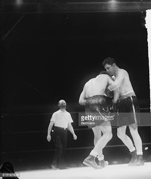 James Braddock his face bruised and swollen hangs onto Joe Louis in a clinch in the seventh round of their title bout in Chicago