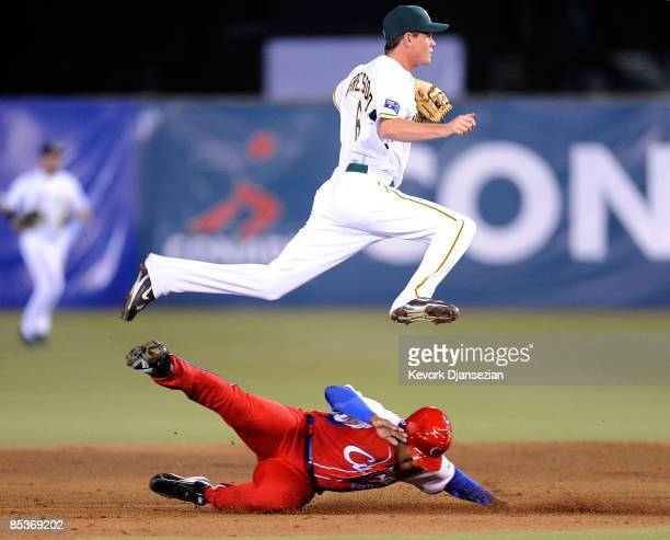 James Brasford secodn baseman of Australia leaps over Alfredo Despaigne of Cuba to avoid a collision after turning a double play during the second...