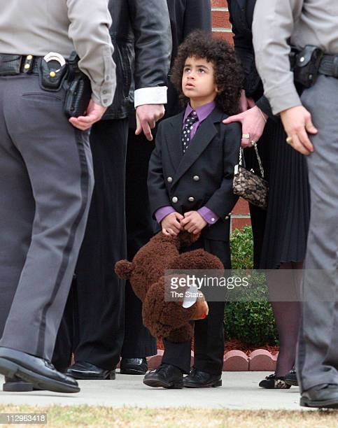 James Brown II listens as a police officer speaks with his mother Tomi Rae Hynie before making his way into Carpentersville Baptist church for his...