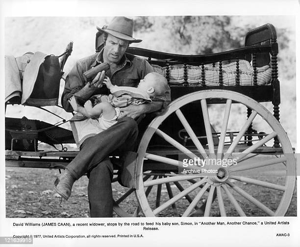 James Caan stops to feed his baby son in a scene from the film 'Another Man Another Chance' 1977