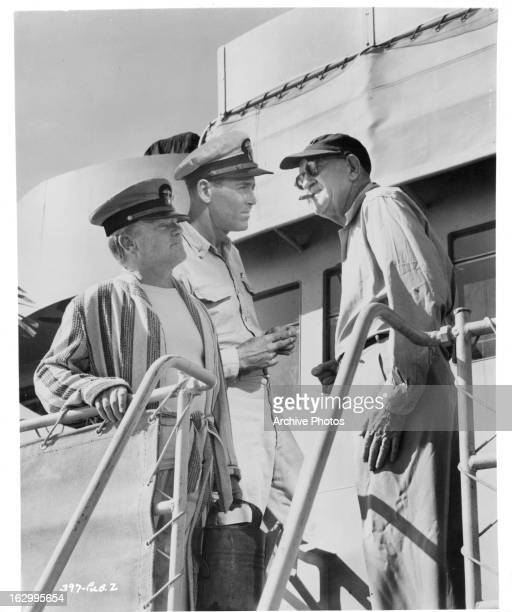 James Cagney and Henry Fonda talk to director John Ford on set of the film 'Mister Roberts' 1955