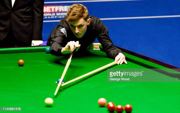 James Cahill lines up a shot against Ronnie O'Sullivan in the opening round of the world snooker championship at Crucible Theatre on April 23 2019 in...