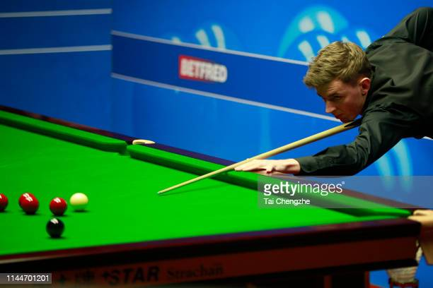 James Cahill of England plays a shot in the first round match against Ronnie O'Sullivan of England during day four of the 2019 Betfred World Snooker...
