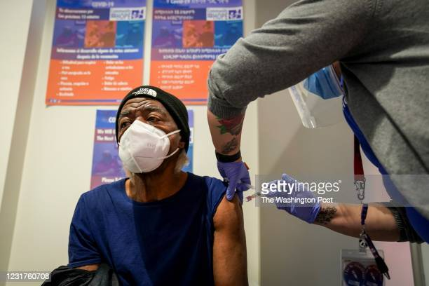 James Campbell R, receives a coronavirus vaccine shot from medical assistant Cindy Alonzo at Community of Hope health clinic on February 26 in...