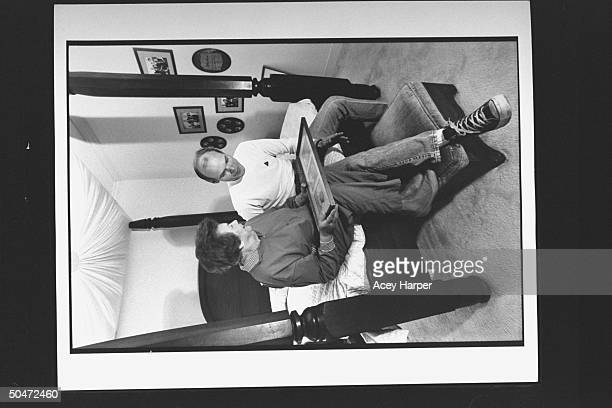 James Carville pol consultant for Dem Pres cand Bill Clinton going over photos w his mom Lucille as they sit on fourposter bed at her home
