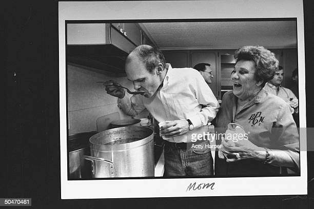 James Carville pol consultant for Dem Pres cand Bill Clinton tasting a spoonful of soup from large pot on stove while his mom Lucille laughs while...