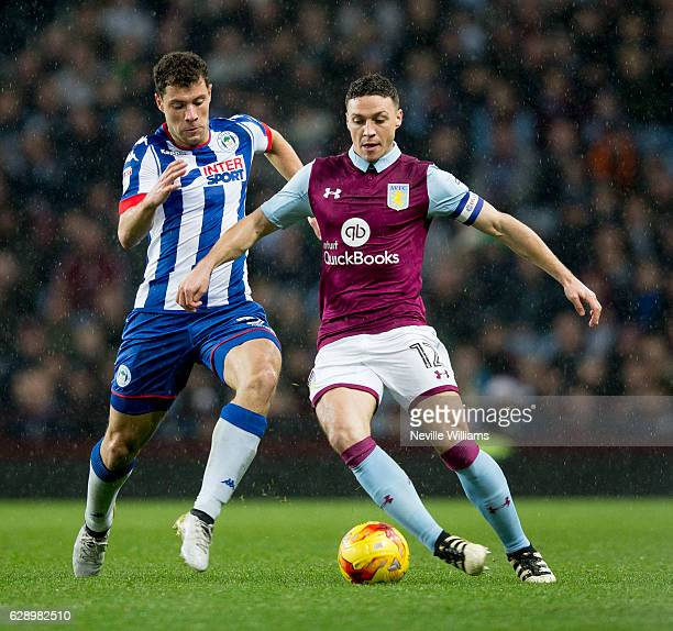 James Chester of Aston Villa is challenged by Yanic Wildschut of Wigan Athletic during the Sky Bet Championship match between Aston Villa and Wigan...
