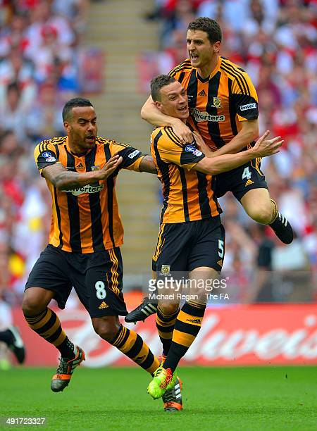 James Chester of Hull City celebrates with team-mates Alex Bruce and Tom Huddlestone after scoring the opening goal during the FA Cup with Budweiser...
