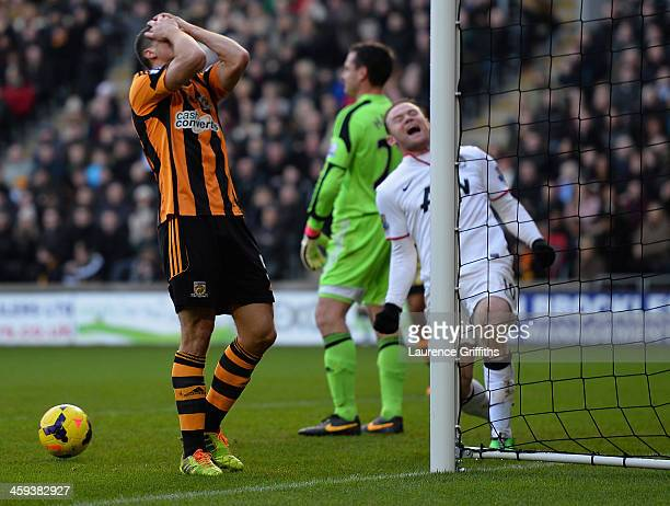James Chester of Hull scores an own goal in front of Wayne Rooney of Manchester United during the Barclays Premier League match between Hull City and...