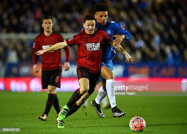 James Chester of West Bromwich Albion shields the ball from Lee Angol of Peterborough during the Emirates FA Cup fourth round replay match between...