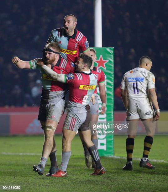 James Chisholm of Harlequins celebrates with team mates after scoring a try during the European Rugby Champions Cup match between Harlequins and...