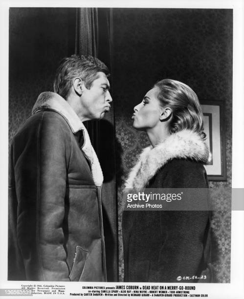 James Coburn and Camilla Sparv pucker up for each other in a scene from the film 'Dead Heat On A MerryGoRound' 1966