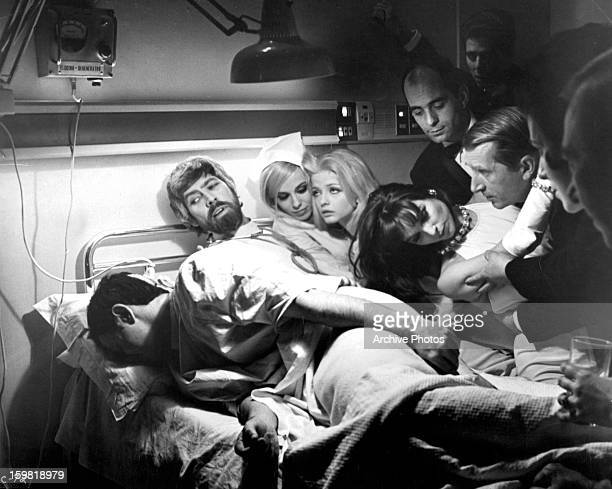 James Coburn Ewa Aulin and others crowd on and around a hospital bed in a scene from the film 'Candy' 1968