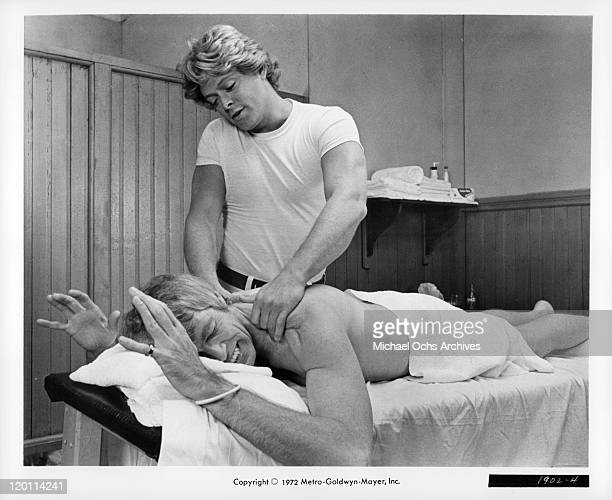 James Coburn gets massage from Michael Blodgett in a scene from the film 'The Carey Treatment' 1972
