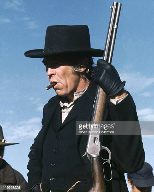 James Coburn US actor carrying a shotgun and wearing a black hat and jacket while smoking a cigar in a publicity still issued for the film 'Pat...