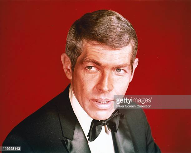 James Coburn US actor wearing a black dinner jacket and black bow tie in a studio portrait against a red background circa 1970