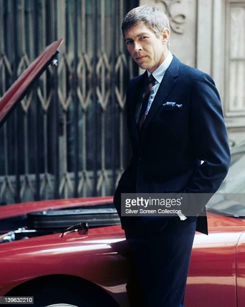 James Coburn US actor wearing a dark blue suit with his hands in the pockets of his trousers posing beside a red sports car circa 1970