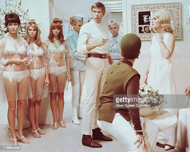 James Coburn US actor wearing a white polo neck jumper and white trousers surrounded by a group of women in a publicity still issued for the film 'In...