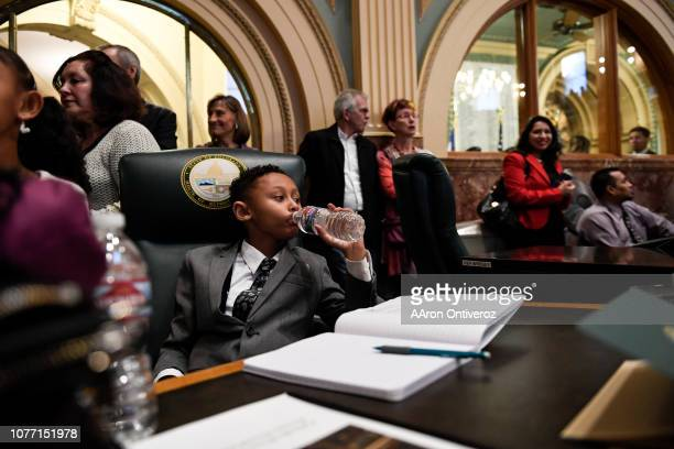James Coleman Jr sits in his father Rep James Coleman Sr's chair during the first day of the 2019 Colorado Legislative Session at the capitol on...