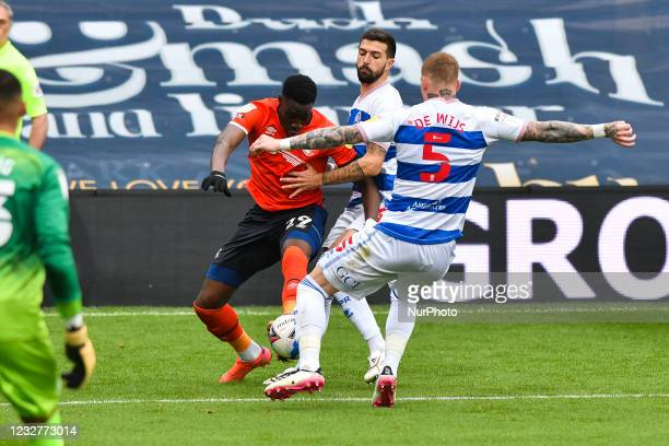 James Collins of Luton town battles for possession with Yoann Barbet of QPR and Jordy de Wijs of QPR during the Sky Bet Championship match between...