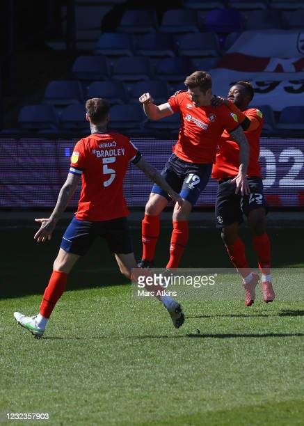 James Collins of Luton Town celebrates scoring the opening goal from a penalty with Sonny Bradley and Kazenga LuaLua during the Sky Bet Championship...