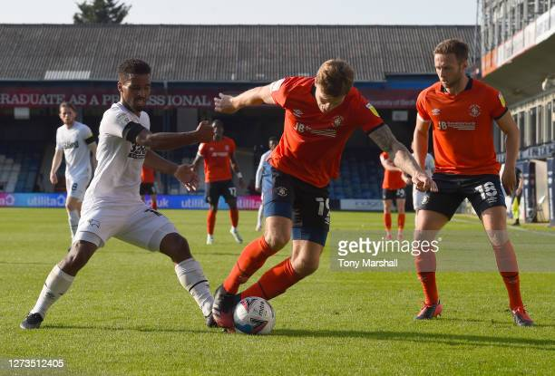 James Collins of Luton Town is tackled by Nathan Byrne of Derby County during the Sky Bet Championship match between Luton Town and Derby County at...