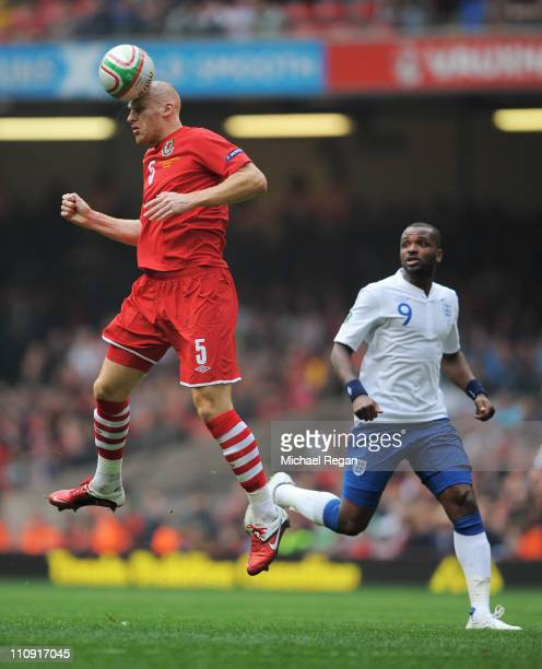 James Collins of Wales wins a header watched by Darren Bent of England during the UEFA EURO 2012 Group G qualifying match between Wales and England...