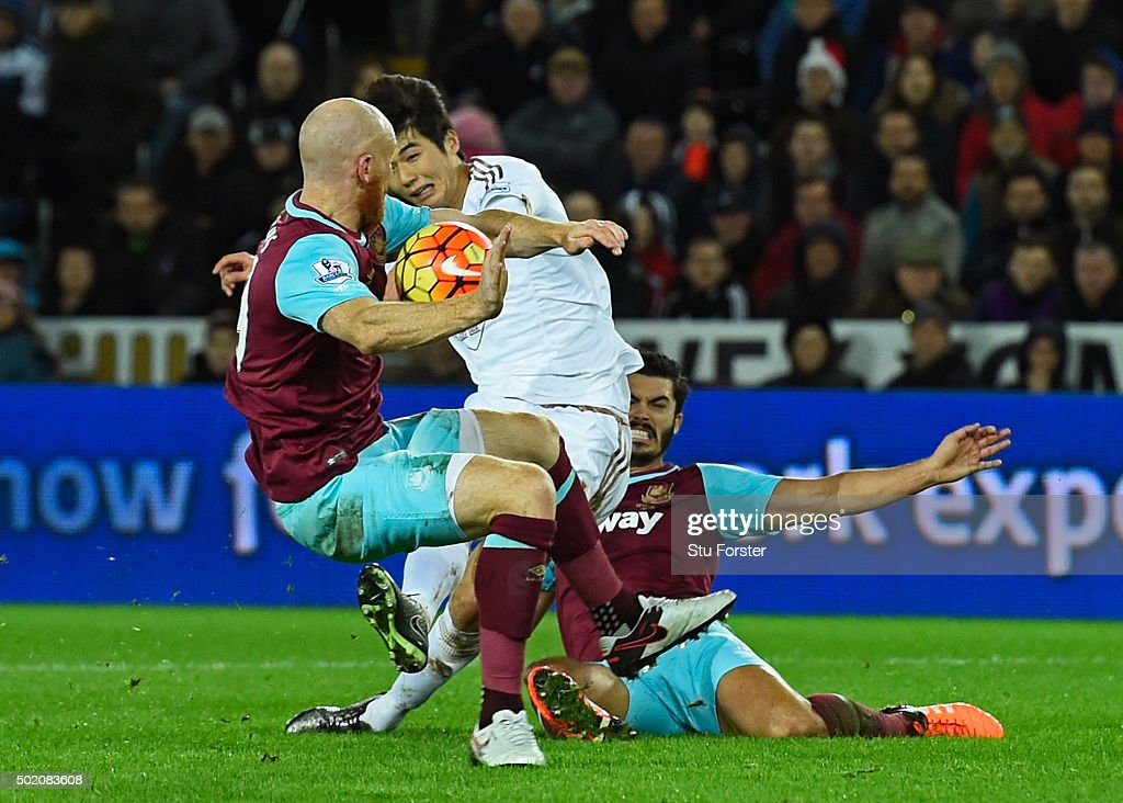 James Collins of West Ham appears to handle the shot from Ki Sung-Yeung of Swansea City during the Barclays Premier League match between Swansea City and West Ham United at the Liberty Stadium on December 20, 2015 in Swansea, Wales.