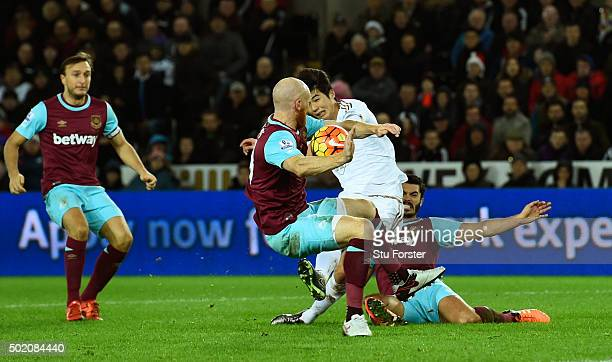 James Collins of West Ham appears to handle the shot from Ki SungYeung of Swansea City during the Barclays Premier League match between Swansea City...