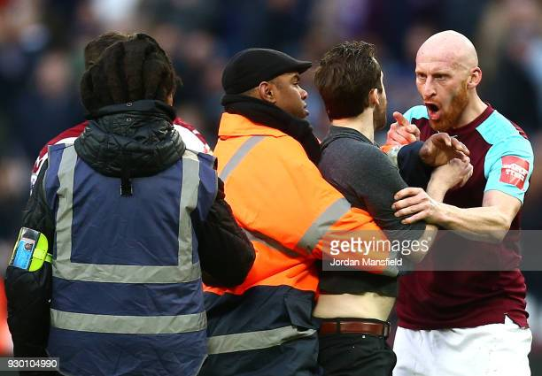 James Collins of West Ham United confronts a pitch invader during the Premier League match between West Ham United and Burnley at London Stadium on...