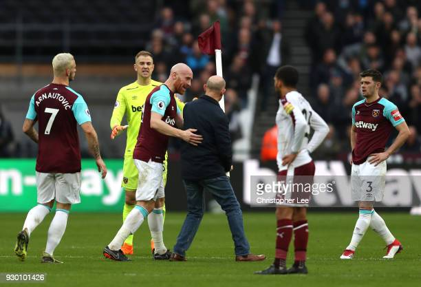 James Collins of West Ham United confronts a pitch Invader who stole the corner flag during the Premier League match between West Ham United and...